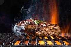 Biftecks de boeuf sur le gril avec des flammes Images stock