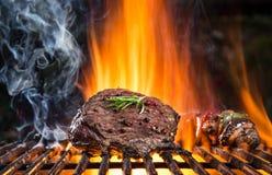 Biftecks de boeuf sur le gril avec des flammes Photos stock