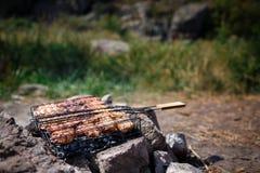 Biftecks de boeuf sur le gril avec des flammes De la belle viande sur le gril est faite frire sur le charbon de bois Jeunes adult Photo stock