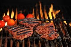 Biftecks de boeuf sur le gril chaud de BBQ avec les flammes lumineuses Images libres de droits