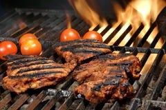 Biftecks de boeuf sur le gril chaud de BBQ avec les flammes lumineuses Image stock