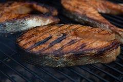 Biftecks de poissons rouges saumonés sur le gril flamboyant images libres de droits