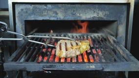 Biftecks juteux délicieux de tabagisme de viande sur le gril sur le feu et le barbecue banque de vidéos