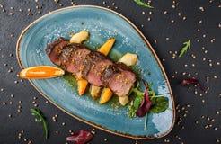 Biftecks juteux de sein de canard avec le fruit, la mangue, la pomme et la sauce caram?lis?s de l'orange du plat au-dessus du fon photos stock
