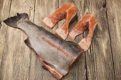 Biftecks norvégiens frais de truite arc-en-ciel se trouvant sur le fond en bois Image stock