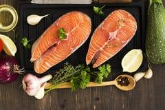 Biftecks saumonés crus au-dessus de fond en bois Images libres de droits