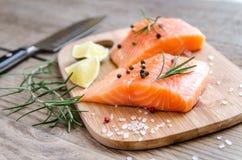 Biftecks saumonés crus sur le conseil en bois Images stock