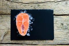 Biftecks saumonés sur la glace sur la vue supérieure en bois noire de table concept de nourriture pour poissons Copiez l'espace Photo stock