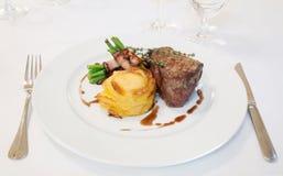 Biftek avec des haricots en lard images stock