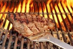 Biftek rôti sur la spatule au-dessus d'un gril chaud de BBQ Photo stock