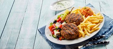 Bifteki, or Greek meat balls, with salad and chips. Bifteki, or Greek meat balls, with salad, tomato rice pilaf and fried potato chips on an oval platter with royalty free stock image