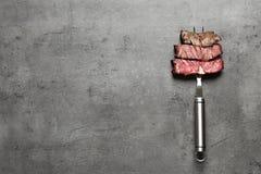 Bifurcación con los pedazos de carne asada a la parilla deliciosa en el fondo gris, visión superior fotos de archivo