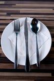 Bifurcación, cuchara y cuchillo en la placa blanca Fotografía de archivo
