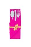 Bifurcación, cuchara y cuchillo en paño rosado con el arco de oro aislado Imagen de archivo libre de regalías
