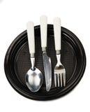Bifurcación, cuchillo y cuchara en una placa plástica negra Foto de archivo libre de regalías