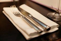 Bifurcación, cuchillo y servilleta en la tabla del restaurante, luz caliente Fotos de archivo libres de regalías