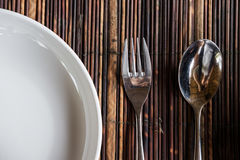 Bifurcación del primer con la cuchara y plato blanco en tablemat de madera foto de archivo