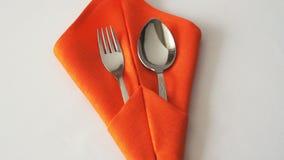 Bifurcación y cuchara Bifurcación y cuchara en servilleta de la materia textil en la tabla almacen de video