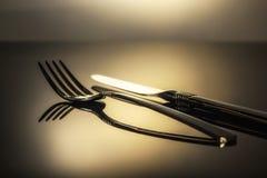 Bifurcación y cuchillo en la tabla en un haz de luz Imagen de archivo libre de regalías