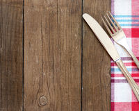 Bifurcación y cuchillo en la toalla de cocina y la tabla de madera vieja imagenes de archivo