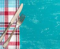Bifurcación y cuchillo en servilleta en la madera de la turquesa Imagen de archivo libre de regalías