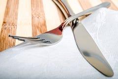 Bifurcación y cuchillo en una servilleta blanca y un tablero de madera Imagen de archivo