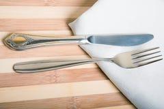 Bifurcación y cuchillo en una servilleta blanca y un tablero de madera Imagen de archivo libre de regalías