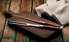 Bifurcación y cuchillo para la carne en el primer del tablero foto de archivo libre de regalías