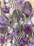 Bifurcaciones y cucharas con las flores frescas Imagen de archivo