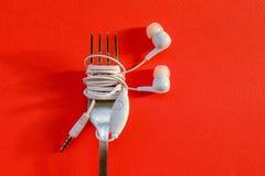 Bifurque con los auriculares en smartphone en fondo del color Diseño del arte del concepto Foto de archivo libre de regalías