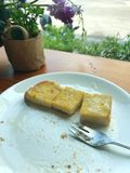 Bifurque-se na placa do pão brindado com manteiga e leite condensado no café da sobremesa imagem de stock