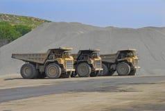 Big 85 ton dump trucks. Three 85 ton capacity Caterpillar dump trucks at stone quarry Stock Photography