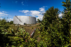 Abandoned Oil Refinery Gas Tank and Rusty Pipeline royalty free stock photo