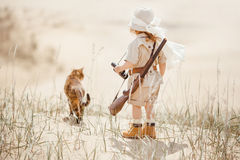 Big advantures in desert. Concept of travel and fascinating adventures. hild in suit of treasures seeker like Indiana Jones in the desert whit wild cat similar royalty free stock photo