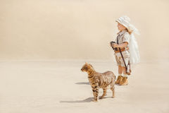 Big adventures in desert. Concept of travel and fascinating adventures. child in suit of treasures seeker like Indiana Jones in the desert whit wild cat similar Royalty Free Stock Image