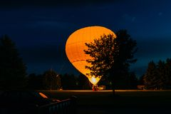 Big air balloon and flame of powerful gas which heats it with hot air during evening in garden, ready to fly in sky. Romantic. Flight concept stock photo