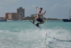 Big Air on a Wakeboard Off of Aruba`s Coast. Wakeboarder jumping and getting big air off the coast of Aruba Royalty Free Stock Images