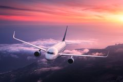 Big airplane is flying in red sky over the clouds Stock Photo