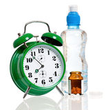 Big alarm clock with bottle of water and pills Royalty Free Stock Image