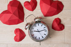 Big alarm clock with red polygonal paper heart shapes Royalty Free Stock Image