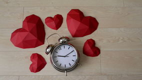 Big alarm clock with red polygonal paper heart shapes stock video