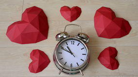 Big alarm clock with red polygonal paper heart shapes stock footage