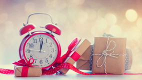 Big alarm clock, red ribbon and beautiful gifts on the fairy lig Stock Photos