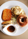 Big American breakfast. A photograph showing a big American style breakfast with bagel, scrambled eggs, hash brown, sausages, and some alfalfa sprouts in the Stock Image