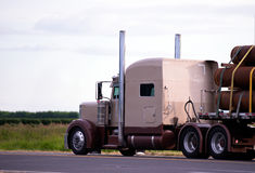 Big American classic rig semi truck transporting big pipes Royalty Free Stock Image