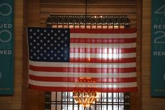 Big american flag in main concourse of Grand central station. Big American flag hanging in the main concourse of Grand central station. Which is a Landmark in royalty free stock image