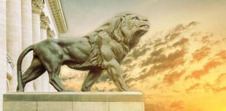 Big ancient archeology statue of lion with burning sun Stock Photography