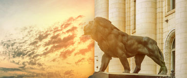 Big ancient archeology statue of lion with burning sun Stock Image
