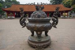 A Big antique bronze incense burner with the House of Ceremonies in the background at Temple of Literature Original built in 1070. In Hanoi, Vietnam Stock Photography