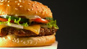 Big appetizing burger with meat cutlet, onion, vegetables, melted cheese, lettuce and mayonnaise sauce. Isolated. Hamburger rotates on dark background, close-up stock video footage